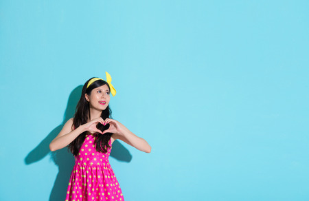 beautiful smiling woman showing love heart shape gesture standing on blue background and wearing cute dress looking at empty area.