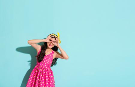 mooie vrouwengebaren ok om haar ogen te behandelen en het tonen van de mooie kleding met roze kleding en gele haarband op de blauwe muurachtergrond met leeg gebied over copyspace.