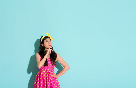 sweet asian girl student thinking about solving the problem by standing on the blue wall and wearing a lovely dress skirt emotion looking at the blank area of the copyspace background.