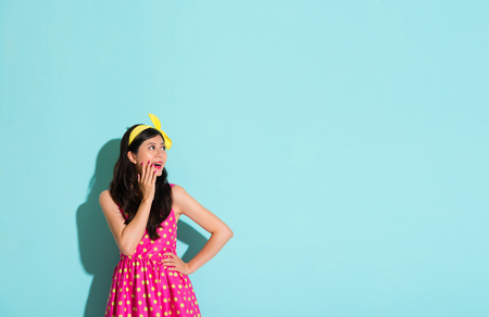 cheerful woman wearing a cute colorful dresses standing on a blue background with surprising face expression on blank copy space happy looking at blank advertising content area.