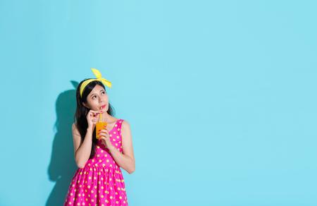 fantasize: beauty lovely woman thinking daydreaming isolated on blue background when she enjoying drinking cooling orange juice. Stock Photo