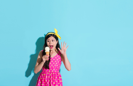 young beautiful woman wearing cute dress clothing standing on blue background and looking at delicious ice cream feeling surprised.