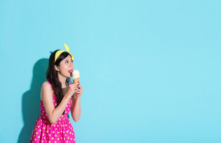 beautiful attractive girl lipping cooling ice cream and wearing summer cute dress looking at empty area of blue background daydreaming. Stock Photo