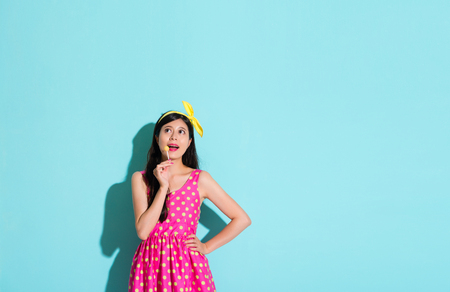 happy pretty woman wearing cute dress clothing standing in blue background and holding lollypop candy making thinking posing.