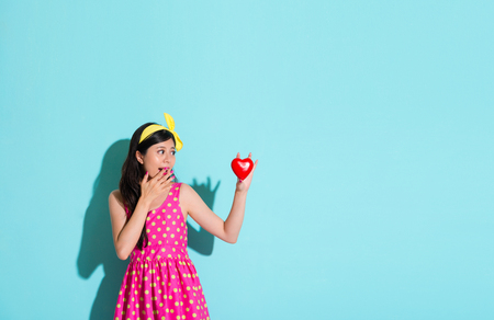 lovely elegant girl looking at heart shaped in blue background and feeling surprised.