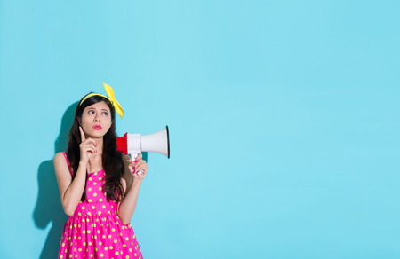 sweet elegant lady in blue background daydreaming thinking idea and wearing cute dress holding megaphone looking at empty area.