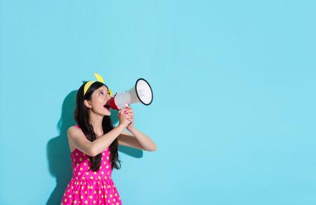 happy beautiful woman using megaphone speaking information and wearing pink cute dress in blue wall background. Standard-Bild