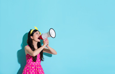happy beautiful woman using megaphone speaking information and wearing pink cute dress in blue wall background. Фото со стока