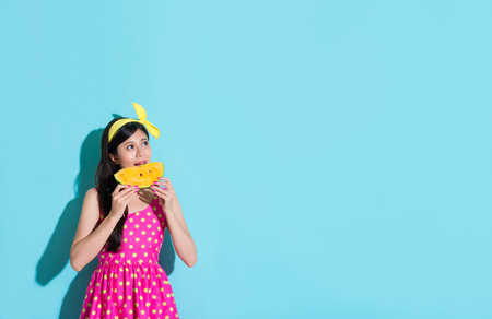 beauty attractive girl wearing cute dress clothing isolated on blue wall background and eating watermelon looking at empty area daydreaming.