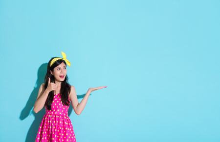 smiling happy girl wearing cute dress standing on blue background making displaying posing and showing thumb up gesture looking at empty area.