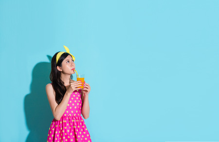 young beautiful woman wearing cute dress standing on blue background and drinking orange juice looking at above daydreaming.