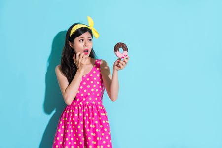 jonge schoonheid meisje kijken naar zoete smakelijke donut gevoel bang en bezorgd tand verval ziekte probleem geïsoleerd op blauwe achtergrond.