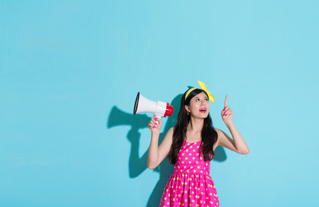 fantasize: beautiful smiling woman pointing above showing empty area and holding loudspeaker standing on blue background with summer cute dress. Stock Photo