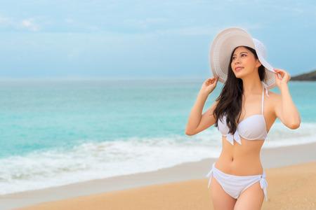 エレガントなアジアのビキニ女性が考え、夏休み中に海の風を吹く美しい copyspace 空を見て美しい島旅行に行きます。 写真素材
