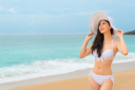 elegant asian bikini woman going to the beautiful island travel looking at the beautiful copyspace sky thinking and blowing ocean winds during the summer vacation.