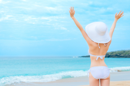 back view photo of young beauty girl wearing bikini clothing with hat standing on beach and opening arms enjoying seaside landscape.
