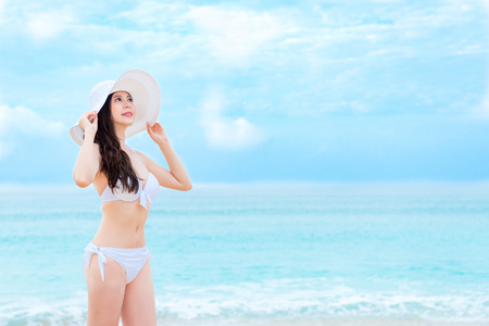 attractive beauty girl traveler wearing sexy bikini clothing with white hat standing on beach and looking at sky daydreaming. Stock Photo