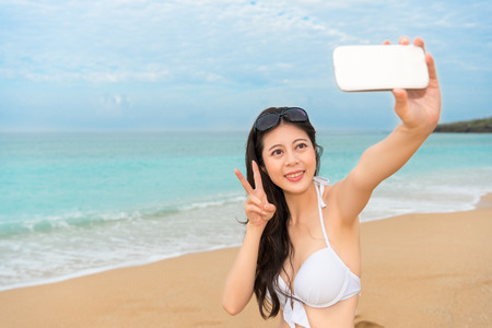 5de2f84c32297 selfie travel woman wearing bikini clothing using mobile cell phone on beach  cheerful taking pictures with