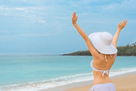 スリムな女性が身に着けているビキニで浜に立って、美しい青い海の水の風景に直面しては、空 copyspace で海の風を楽しむことに彼女の手を発生しま