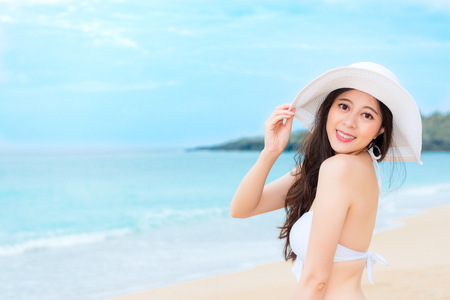 smiling pretty woman looking at camera when she wearing bikini with summer hat going to island country travel during vacation holiday.