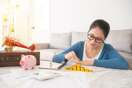 asian chinese woman opening pink piggybank deposit savings and calculate the amount of gold coins on the bill table in the living room at home for travel vacation with her friends.