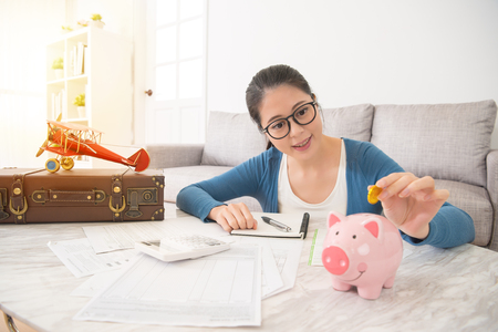 beautiful woman at home carefully record the family bill cost and saving gold coins to the piggy bank hoping to travel with the family on the children summer vacation.