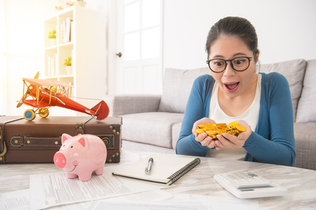 young mother looking at the hands holding many gold coins stack and surprise celebration of the deposit enough to plan family travel from the piggy bank and personal account fund.