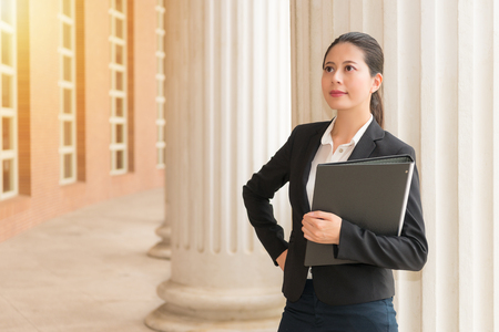 law suit: pretty smiling female lawyer eyes looking at sun holding legal case file get ready opening court session standing in courtyard corridor outdoor. Stock Photo