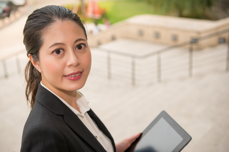 closeup photo of business lawyer using mobile pad computer prepare information for session and search relevant laws and regulations in court outdoor. Stock Photo