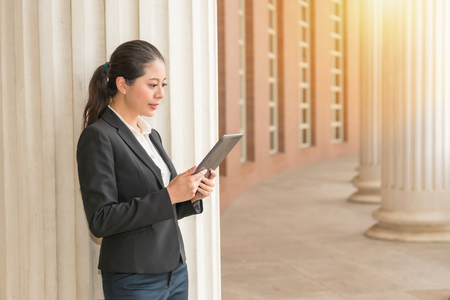 seriously business woman standing in classical court building prepare legal meeting information through digital tablet computer looking online website with sun.