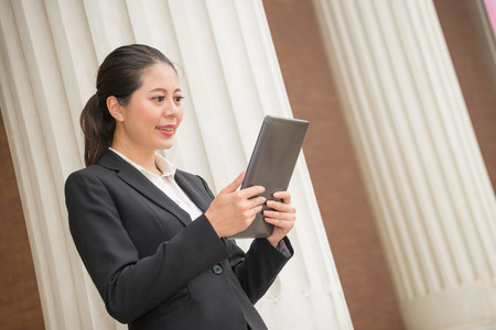 smiling business woman lawyer watching mobile computer pad screen finding law legal case litigation success with court beam pillar building background. Banco de Imagens