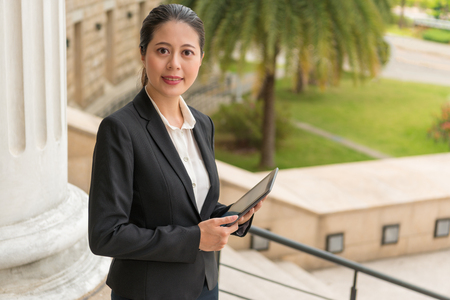 smiling friendly businesswoman holding digital tablet computer wearing suit clothing standing in classical government court use online service dealing with legal cases.