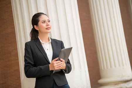 beautiful female lawyer holding digital tablet computer standing in front of court through internet to provide customers online consulting services. Banque d'images