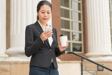 beautiful young businesswoman using mobile phone contact company customer and search browse legal website holding coffee cup relax in court outdoor.