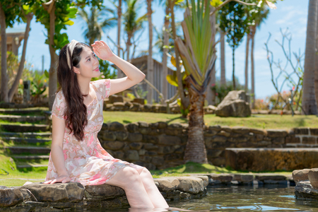 elegant young woman sitting on pond side and making searching posing viewing landscape when she travel in tropical nation. Stock Photo