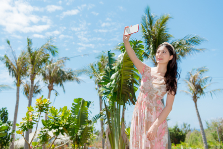 sweet woman going to tropical nation travel and using mobile smartphone taking selfie picture with coconut tree. 版權商用圖片