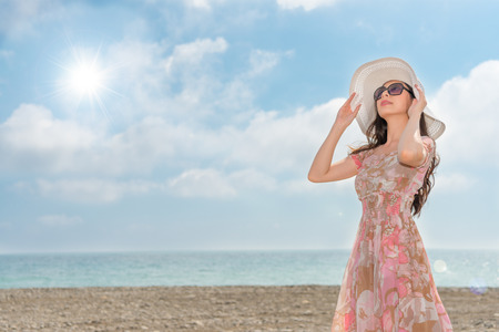 asian woman wearing elegant dress clothing and wearing a white hat and sunglasses happy looking at the dazzling sun day dreaming copyspace standing on the clean beach in the family vacation.