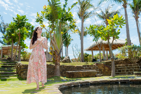elegant beauty woman traveler holding mobile cell phone and walking in coconut tree yard relaxing enjoying vacation with pond.