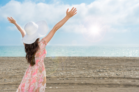 woman raise her arms and open hands showing looking at the sunny sky over copyspace immersed in the sea breeze and beautiful scenery in the summer holidays with pretty dress back view. Фото со стока