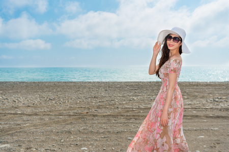 asian chinese girl happy to travel on the sea standing on the beach with copyspace area experience the cool sea breeze winds wearing the sunglasses in the summer afternoon. Stock Photo