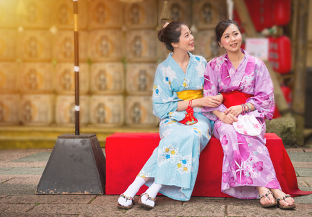 best girlfriends sitting on the culture street in Japanese festival with neat lantern background, women wearing japan traditional kimono enjoying art decoration during travel with copyspace. Фото со стока