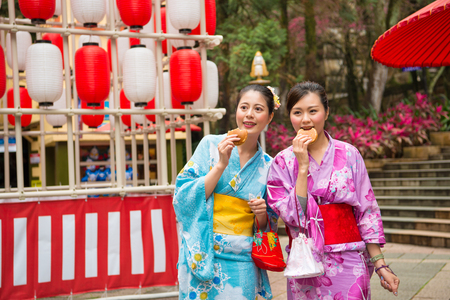 female tourists going to japan participate famous festivals celebrating wearing traditional kimono and eating delicious dorayaki food together walking in the streets of cultural lanterns.