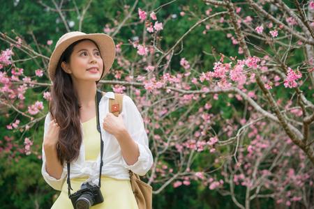 아름 다운 미소 관광 여자 유명한 사쿠라 나무 공원에서 벚꽃 꽃을보고 일본 여행에서 봄 시즌 휴가를 즐기는.