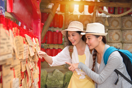 smiling girlfriends travelers looking at pray board wooden plaques and pointing showing gesture during travel in japan buddhist temple. Stock Photo