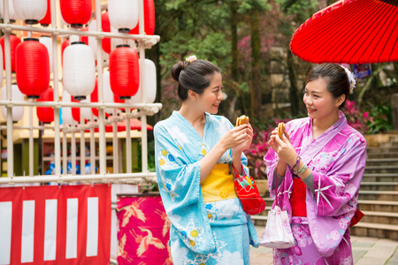 japanese women going to the local shrine tasting delicious dorayaki snacks sharing together enjoy the festival lantern decoration wearing traditional kimono clothing. Stock Photo