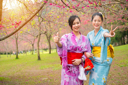 beautiful chinese wearing traditional kimono standing on the cherry blossom park cheerful showing gesture thumb up and victor smiling pose portrait during sightseeing holidays