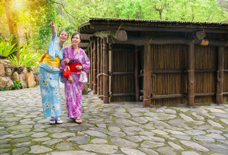 asian young girlfriends wearing kimono clothing together pointing up with watching nature view and near old japan wooden house outside on the travel vacation at sunshine day with copyspace. Фото со стока