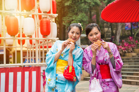 young female students wearing the kimono costume dress to the celebration street walking and eating the dorayaki cake together in the summer afternoon time with sunshine. Stock Photo