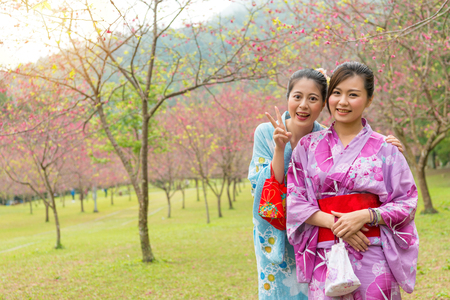 cheerful women girlfriends showing victory happy gesture taking photo together and wearing traditional kimono in cherry blossoming garden during  japan vacation holiday. Stock Photo