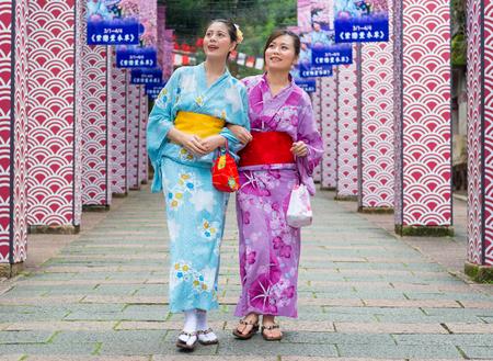 伝統的な服を着てハッピーかわいいガール フレンドのドレス着物日本の祭りのお祝いを一緒に結合して、夏休みで日本文化を表示する歴史経路上を 写真素材